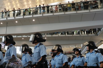 Police take positions as pro-democracy protesters gather outside the airport in Hong Kong on Sunday.