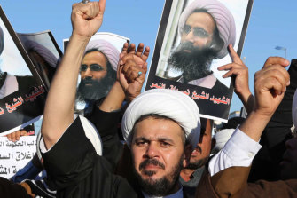 Iraqi Shiites protest against the Saudi government as they hold posters showing Sheikh Nimr al-Nimr, who was executed in Saudi Arabia.