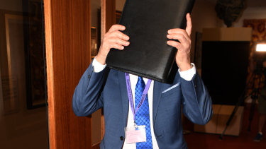 Mr Miller covers his face as he arrives for the parliamentary inquiry hearing.