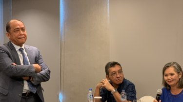 Exiled Cambodian opposition leader Mu Sochua, right, speaks at a press conference in Jakarta, next to  Indonesian activist Darmawan. Cambodian ambassador to Indonesia Hor Nam Bora - who tried to stop the event - looms over the pair.