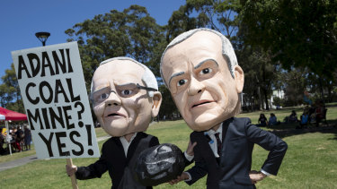 Anti-Adani coalmine protesters in Sydney donned bobble heads resembling Opposition Leader Bill Shorten and Prime Minister Scott Morrison to urge Labor to rule out matching the government's support for the mine.