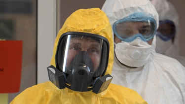 Russian President Vladimir Putin wearing a protective suit enters a hall during his visit to the hospital for coronavirus patients in Kommunarka, outside Moscow.