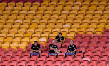 Rabbitohs coach Wayne Bennett and his coaching staff in the empty stands for their match against the Broncos in round two.