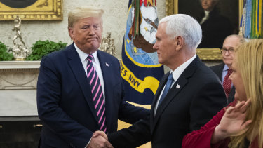 US President Donald Trump, left, shakes hands with Vice President Mike Pence during a meeting in the Oval Office a day after he was impeached.
