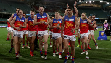 Ton up: Charlie Cameron leads his team from the field after his 100th game for the Lions.