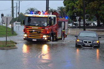 Vehicles get stuck in flooded streets in Corio this afternoon.