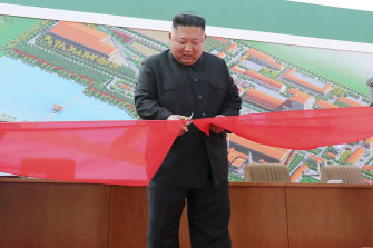 Kim Jong-un, centre, cuts a ribbon during his visit to a fertiliser factory in South Pyongan on Friday.