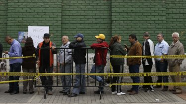 People wait in line for the voting booths to open during the presidential election in Bogota, Colombia, on Sunday.