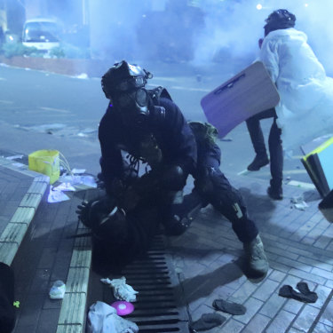 A policeman detains a protester outside of Hong Kong Polytechnic University as police storm the campus  on November 18.