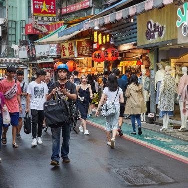 Tourists and locals walk around a night market in Taipei in 2018.