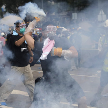 A demonstrator throws a canister of tear gas back at police during protests outside the Legislative Council on June 12.