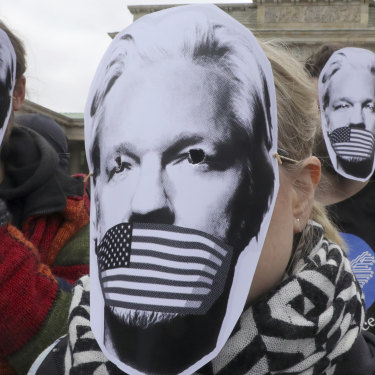People in Berlin wear masks to protest against Assange's possible extradition to the US.