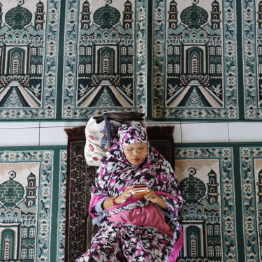A woman rests at a mosque on the first day of Ramadan in Bali.