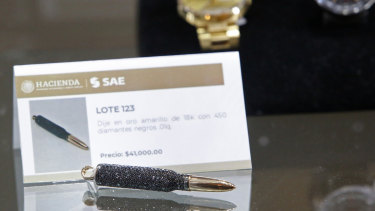 A necklace pendant made of yellow gold with 450 black diamonds in the shape of a bullet is displayed during the auction of items seized from purported drug dealers and tax cheats.