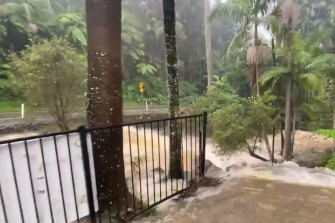 A raging torrent of water is threatening the Curtis Falls Cafe. Council crews are trying to clear blocked drains across the road.