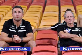 Sam Burgess (left) and Rabbitohs coach Wayne Bennett sitting in the empty grandstands during the round two NRL match between the Brisbane Broncos and South Sydney Rabbitohs at Suncorp Stadium in March.