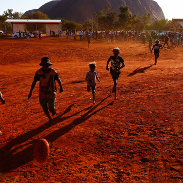 Mutitjulu children playing footy during the closing ceremony in the shadow of Uluru.
