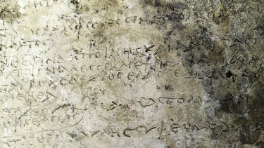 A slab inscribed with verses from the Odyssey's Book written in ancient Greek.