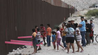Children play on seesaws installed between the border fence at the US-Mexico border.