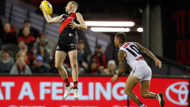 Nick Hind takes a stellar mark against Michael Walters and the Dockers at Marvel Stadium.