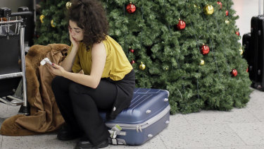 A woman waits in the departures area at Gatwick Airport.