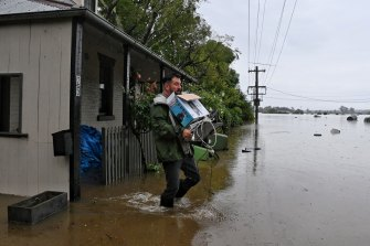 Ben Sullivan retrieves a few last items before he leaves his inundated home in Windsor on Monday morning.