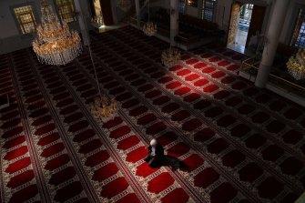 Auburn Gallipoli Mosque General Manager Ergun Genel prays alone due to the coronavirus.