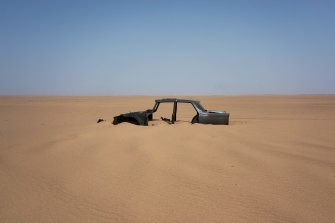 The frame of an abandoned Peugeot rests in Niger's Tenere desert. Once a well-worn roadway for  tourists, the 4500-kilometre route is a favoured path for migrants heading north.
