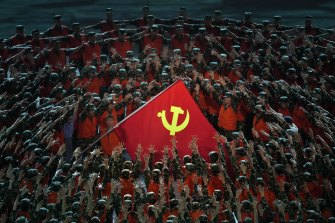 Performers in the role of rescue workers gather around a Communist Party flag during a gala show ahead of the 100th anniversary.