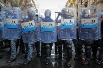 Police officers face demonstrators protesting on the sidelines of the G20 meeting in Italy.