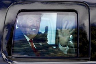 Former President Donald Trump waves to supporters as his motorcade drives through West Palm Beach after he left office.