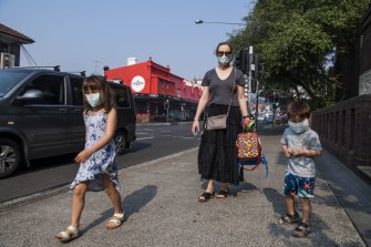 Emily with her children Abigail and Alexander wear face masks on their way to school in Bondi.