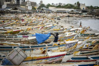 A fisherman dries a sheet next to fishing boats on the beach in Dakar, Senegal.