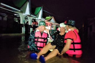 Rescuers carry a woman following the sudden rise in floodwaters as Typhoon Goni hit Batangas province, south of Manila.