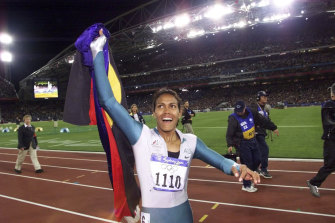 Cathy Freeman celebrates her Sydney Olympic gold medal win with the Aboriginal and Australian flags.