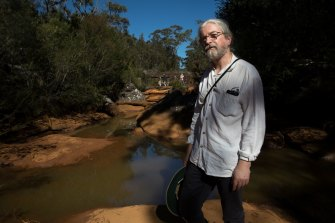 Peter Turner, from the National Parks Association of NSW, examines iron contamination of the Eastern Tributary, in the Woronora catchment area, south of Sydney.