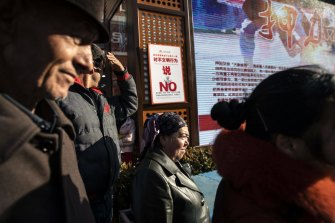 """A sign warning against """"uncivilised behaviour"""" is displayed as spectators watch a street performance in the main bazaar in Urumqi, Xinjiang."""