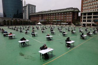 South Koreans wear masks and sit according to social distancing as a preventive measure against the coronavirus during an exam.