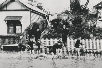 Children ride bicycles in the floodwaters.