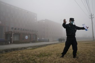 A security person moves journalists away from the Wuhan Institute of Virology after the WHO team arrived in February.