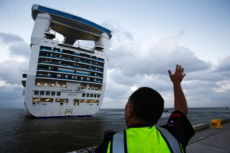 An officer waves off a Caribbean Princess cruise ship in Pasadena, Texas. Princess Cruise Lines' owner, Carnival, will pay a $28 million penalty for pollution breaches.