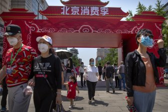 People wearing face masks to protect against the new coronavirus walk at a government event aiming to stimulate consumer demand and consumption in Beijing, Saturday, June 6, 2020.
