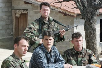 Hashim Thaci, then head of the Kosovo Albanian negotiation team and of the Kosovo Liberation Army political directorate, centre seated, addresses a press conference in a secret location in central Kosovo in 1999.