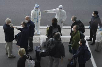A worker in protective coverings directs members of the World Health Organization (WHO) team on their arrival at the airport in Wuhan in central China's Hubei province in January.