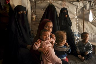Australian Maysa Assaad, 9, holding Shayma Assaada's daughter Mariam (second from left) in the al-Hawl camp.