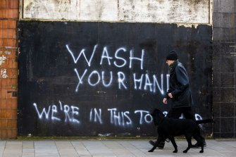 """A man walks his dog past graffiti with the writing, """"Wash Your Hands, We're In This Together"""", in Belfast, Northern Ireland, last month."""