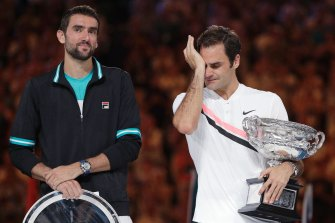 Roger Federer wipes away tears after defeating Croatia's Marin Cilic, left, to win the Australian Open and achieve a grand slam record in 2018.