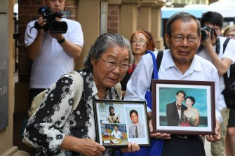 Min Lin's parents hold photos of their murdered relatives outside court in 2017.