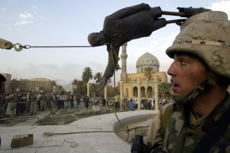 Iraqi civilians and US soldiers pull down a statue of Saddam Hussein in Baghdad in 2003.