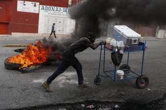In Haiti, a snow cone vendor pushes his cart past a burning barricade on October 15.